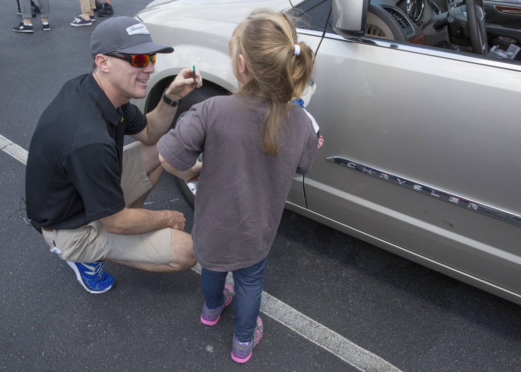 Racing toward Memorial Day Weekend, the unofficial start of the summer driving season, the Goodyear Tire & Rubber Company and NASCAR champion Kevin Harvick (seen here teaching a young fan about tire maintenance), provided free tire checks to consumers at the Concord Mills Mall in Concord, NC to help prepare them leading into National Tire Safety Week. (Jason E. Miczek/AP Images for Goodyear)